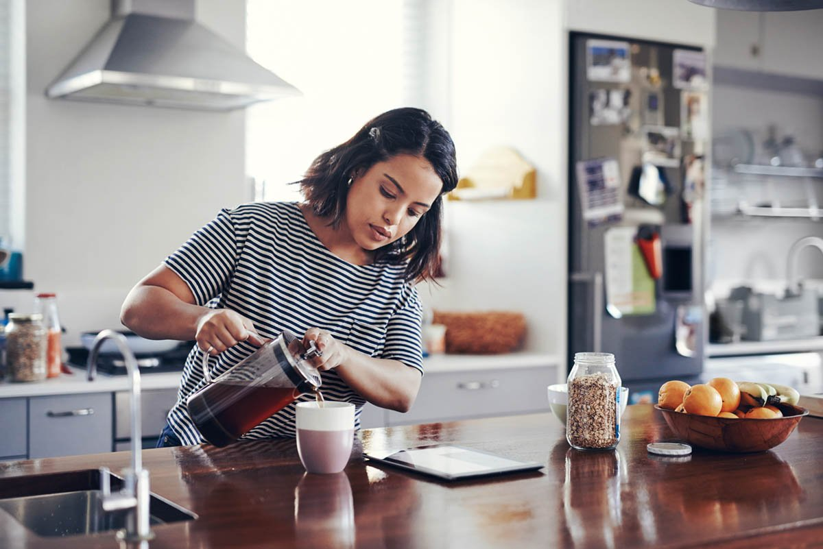 Woman Pouring Coffee on Vacation at a Vacation Property Rental